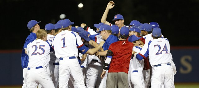 The Jayhawks mob teammate Dakota Smith after Smith's eleventh-inning single drove in teammate Michael Suiter for the win against Wichita State, Tuesday, April 30, 2013 at Hoglund Ballpark. Nick Krug/Journal-World Photo