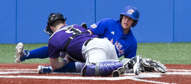Kansas' Michael Suiter looks to the umpire for a call after sliding into home under the tag by Kansas State catcher Blair DeBord during the final game of Kansas' three game home series against Kansas State Sunday at Hoglund Ballpark. The Wildcats swept the series.