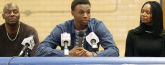 Huntington Prep basketball player Andrew Wiggins, center, flanked by his parents Mitchell Wiggins and Marita Payne-Wiggins, as he announces his commitment to the University of Kansas during a ceremony, Tuesday, May 14, 2013, at St. Joseph High School in Huntington W.Va. The Canadian star, a top prospect, averaged 23.4 points and 11.2 rebounds per game this season for West Virginia&#39;s Huntington Prep. 
