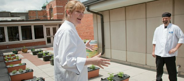 Janna Traver, the executive chef for KU Dining Services, left, and Joe Pruitt, an executive sous chef, discuss and give a tour of the expanded rooftop herb and vegetable garden at the Kansas Union. Ingredients are used in the Market food court and for special dinners.