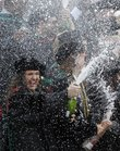 A Master of Arts graduate is lost in a shower of champagne as the school celebrates during commencement ceremonies Sunday, May 19, 2013.