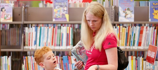 Five-year-old Taylor Brown browses the shelves of kids' books with his mother, Lawrence resident Liz Brown, at the Lawrence Public Library's temporary location in the old Borders building at Seventh and New Hampshire streets earlier this month.