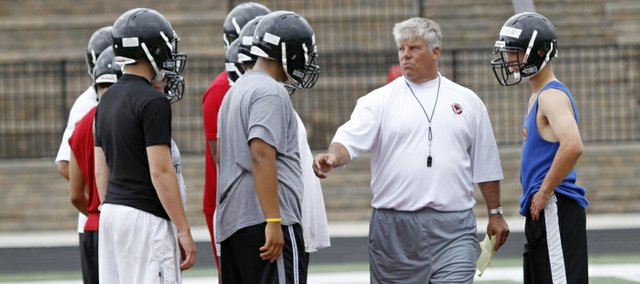 Lawrence High School head football coach Dirk Wedd talks to players about an offensive set during the Lions' football camp, Tuesday, May 28, 2013, at LHS.