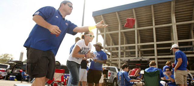 Kansas fans Dan Lewis, Lenexa, and Ann Kindle, Overland Park, toss bean bags while tailgating in the parking lot prior to kickoff against South Dakota State on Saturday, September 1, 2012 at Memorial Stadium. Lewis says he'd been at the stadium tailgating since 5:30 a.m.