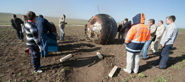 Workers surround the Bion-M1 satellite shortly after it landed near the Russia-Kazakhstan border in late May.