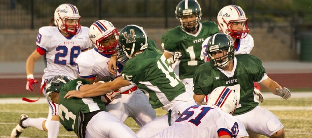 Free State's Stan Skwarlo (3) and Kyle McFarland (15) team up to bring down Olathe North's Elbert Johnson on Friday, Sept. 21, 2012, at FSHS.