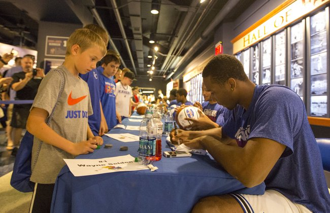 Eight-year-old Jackson Noland waits as Kansas freshman Wayne Selden signs his T-shirt during an autograph session for attendees of Bill Self's basketball camp Sunday at Allen Fieldhouse.