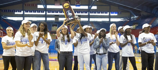 Members of the Kansas University women's track team hold up the national championship trophy in front of a small crowd gathered inside Allen Fieldhouse on Sunday to welcome the team home.