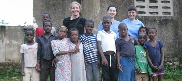 From left, Cindy Mast, a Lawrence physician assistant, Sarah Bradshaw, a Lawrence nursing student, and Shannon Harvey, a former Lawrence resident and nurse, pose for a picture with kids from the Haitian village they provided medical care for last month.