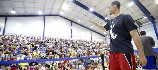 Kansas University forward Perry Ellis waves to a gathering of basketball campers after giving a pep talk about work ethic and maintaining good grades during Bill Self's basketball camp, Tuesday, June 11, 2013, at the Horejsi Center.