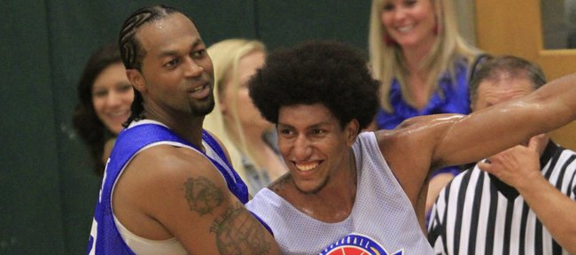 Jeff Graves, left, holds Kevin Young as former Kansas University players squared off during the annual Rock Chalk Roundball Classic, Thursday, June 13, 2013, at Free State High.