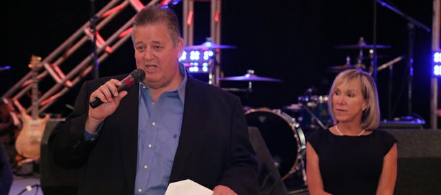 Kansas football coach Charlie Weis, left, and his wife, Maura, take the stage at a fundraiser for their Hannah & Friends charity on Friday, June 21, 2013, in Mayetta. The two-day event will culminate with a golf tournament today.