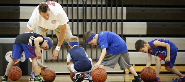 Sacramento Kings player and former Kansas center Cole Aldrich watches as young basketball players have a bit of trouble completing a ball-handling drill on Monday, June 24, 2013, during Aldrich's basketball camp at Olathe Northwest High School.