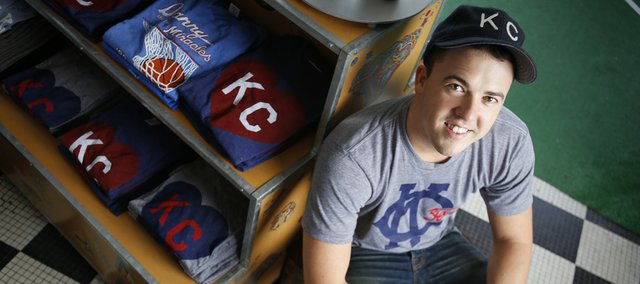 "Chase McAnulty is pictured with several vintage-style T-shirts he designed under his company, ""Charlie Hustle,"" on June 21 at Hobbs, at 700 Massachusetts St."