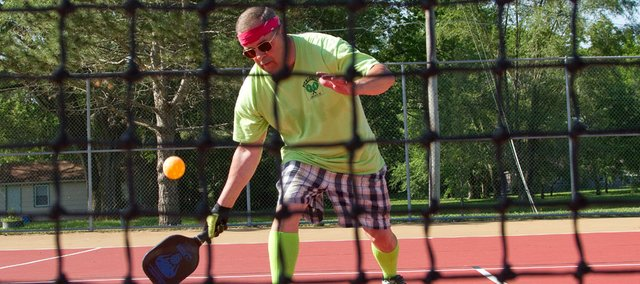 Marshall Hogue, 65, Baldwin, makes a low shot at Lyons Park. He's part of a group in town that has picked up pickleball.