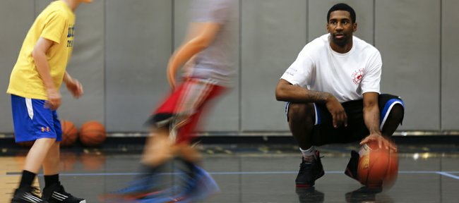 Kansas forward Justin Wesley watches  as campers work on setting picks, Monday, June 24, 2013 during the Cole Aldrich basketball camp at Olathe Northwest High School.