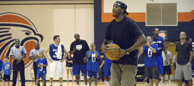 Former Kansas basketball player Mario Chalmers sets to throw the ball during a demonstration at his All Pro Celebrity basketball game Thursday at Olathe East.