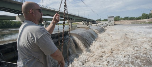 Mark Maxwell, plant manager at Bowersock Mills and Power, lowers a step bridge to check the dam on Tuesday as heavy water pours over it. The Kansas River's high level is a sign of plentiful rainfall that is helping to ease drought conditions.