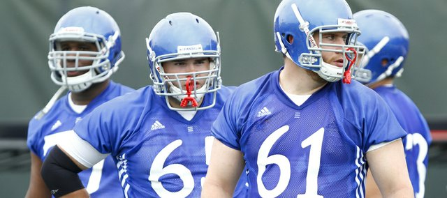 Kansas offensive lineman Pat Lewandowski stares down the line as he and his teammates run through warmups during the first day of football practice on Thursday, Aug. 8, 2013. Nick Krug/Journal-World Photo
