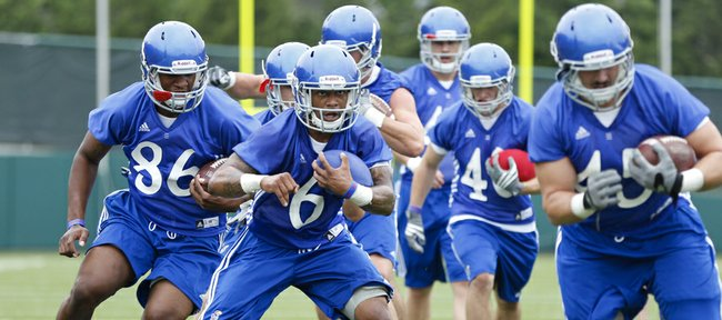 Kansas running back Darrian Miller (6) weaves through some pads as he works out with the running backs and fullback