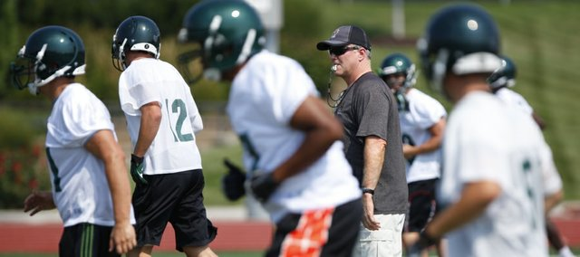Free State head coach Bob Lisher sends the Firebirds through warmup drills with his whistle during the first day of practice on Monday, Aug. 19, 2013 at Free State High School.