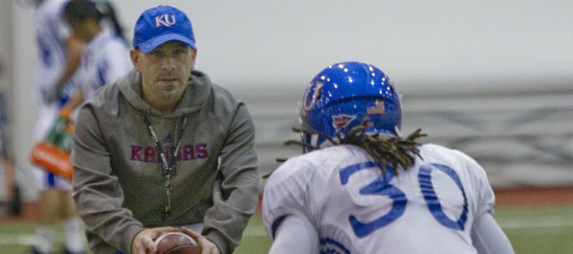 New Kansas University defensive backs coach Scott Vestal works on footwork with red-shirt freshman safety Tevin Shaw during a spring practice on March 9, 2013.