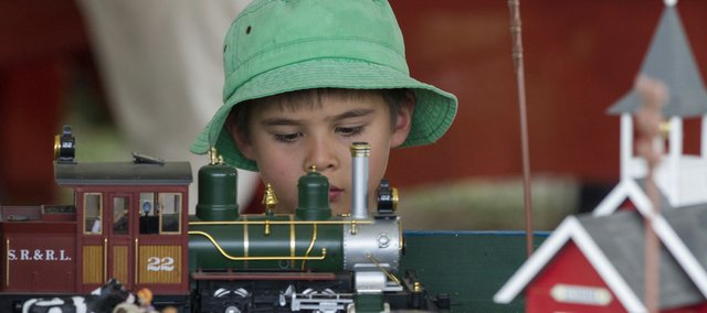 Six-year-old Wesley Janssen, of Olathe, looks over a model train owned by the Midland Railway Depot in Baldwin City during the annual Railfest event Saturday.