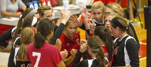 Lawrence High volleyball coach Stephanie Magnuson, center, tries to rally her team during the first set of their volleyball match against Blue Valley Northwest, Tuesday, Sept. 3, 2013, at LHS. The Lions lost, 3-0, in straight sets.