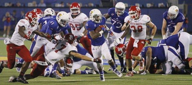 Kansas half-back Darrian Miller (6) runs through the South Dakota defense in KU's 31-14 win against South Dakota at Memorial Stadium, Saturday, Sept. 7, 2013.