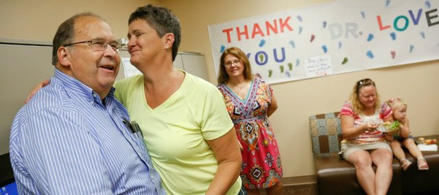 Dr. Charles Loveland gets an emotional hug from registered nurse Lisa Perico during his retirement party at Lawrence Memorial Hospital on Friday, Aug. 23, 2013. Loveland is retiring after 37 years at the hospital. Nick Krug/Journal-World Photo
