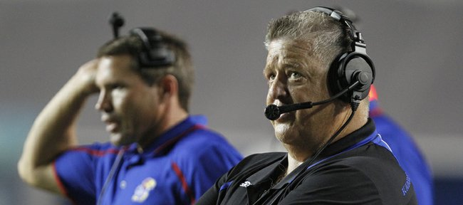 Kansas head coach Charlie Weis looks up at the scoreboard late in the fourth quarter against Rice, Saturday, Sept. 14, 2013 at Rice Stadium in Houston, Texas. At left is linebackers coach Clint Bowen.