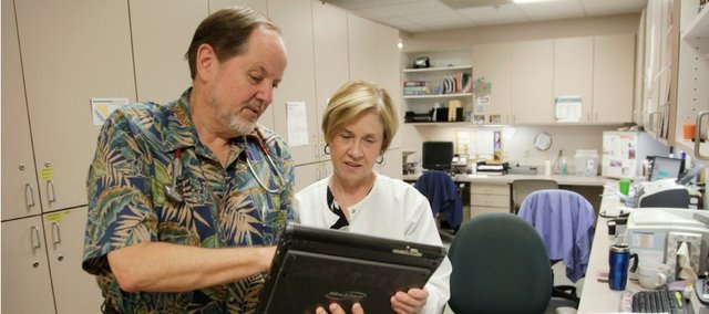 Dr. Steven Bruner and nurse Jan Potts confer at Lawrence Family Medicine & Obstetrics on a recent day. Bruner says he doesn't expect the Affordable Care Act to have much of an effect on local doctors' offices.