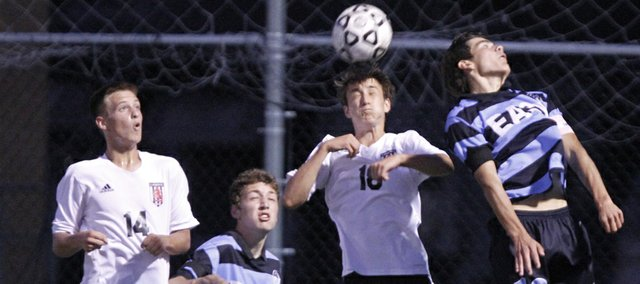 Lawrence High defender Ellis Springe gets up for a header between Shawnee Mission East players Ari Throckmorton, left, and Andrew McClanahan during the first half on Tuesday, Sept. 24, 2013 at Lawrence High School. At left is LHS defender Piper Hubbell.