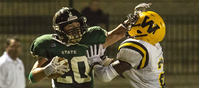 Free State's Keith Loneker (20) gives Shawnee Mission West's Juanyae Stallings (2) a stiff arm as he finds the end zone for a touchdown during their game Friday night at FSHS.