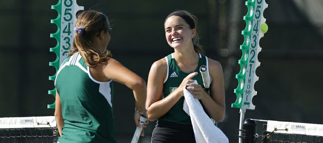 Free State junior Megan McReynolds has a laugh with doubles partner Alexis Czapinski, senior, between sets against Lawrence High on Tuesday, Oct. 1, 2013 at Free State High School.