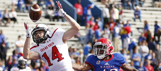 Kansas safety Alex Matlock watches as Texas Tech receiver Dylan Cantrell tips a pass to himself for the Red Raiders' final touchdown against the Jayhawks during the fourth quarter on Saturday, Oct. 5, 2013 at Memorial Stadium.