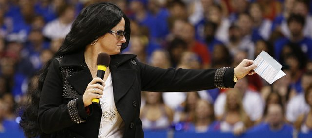 Head coach Bonnie Henrickson, dressed as Cher, points to the crowd as she heads out to the court during the skits and performance of Late Night in the Phog, Friday, Oct. 4, 2013 at Allen Fieldhouse.