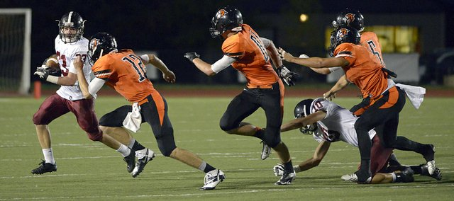 The Lions' Kieran Severa tries to avoid the Shawnee Mission Northwest defense Friday, Oct. 4, 2013, at Shawnee Mission North District Stadium. LHS won, 16-7.