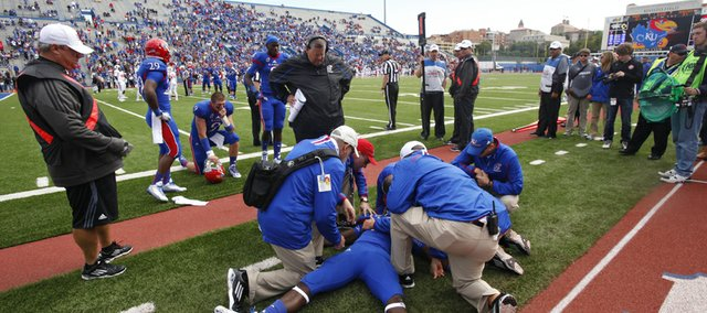 Kansas trainers attend to injured running back Tony Pierson on the sidelines. PIerson left the game during the third quarter on Saturday, Oct. 5, 2013, at Memorial Stadium.
