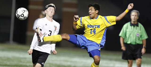 Lawrence High midfielder Parker Davies narrowly pulls back from a flying kick by Olathe South defender Eddy Mortera during the second half on Tuesday, Oct. 8, 2013 at Lawrence High School. Nick Krug/Journal-World Photo
