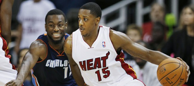 Miami Heat guard Mario Chalmers (15) drives on Charlotte Bobcats guard Kemba Walker during the first quarter of a preseason NBA basketball game Friday, Oct. 11, 2013, in Kansas City, Mo.