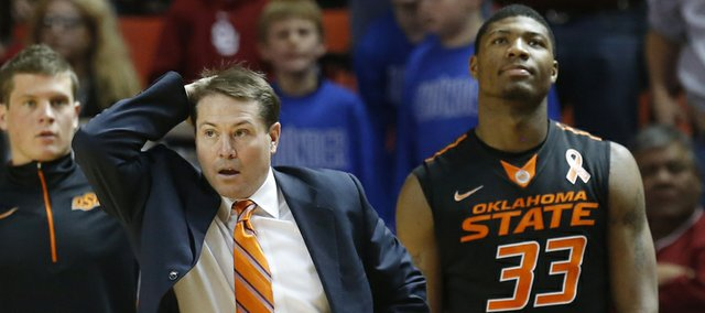 Oklahoma State head coach Travis Ford reacts to an official's call in the second half of an NCAA college basketball game against Oklahoma in Norman, Okla., Saturday, Jan. 12, 2013. Oklahoma State guard Marcus Smart (33) is at right.
