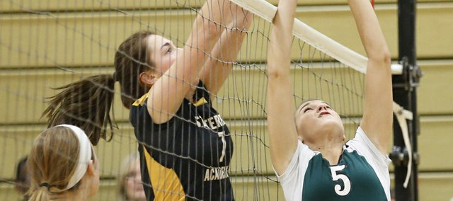 Free State High senior Emilee Kern, right, is stuffed by St. Teresa's Academy player Maddie Torti during a volleyball triangular, Tuesday, Oct. 15, 2013, at FSHS. The point went the Firebirds' way — Torti reached over the net — but Free State lost, 25-13, 25-15.