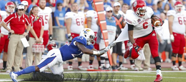 Kansas safety Dexter Linton snags South Dakota recevier Terrance Terry by the jersey before bringing him down during the second quarter on Saturday, Sept. 7, 2013 at Memorial Stadium.