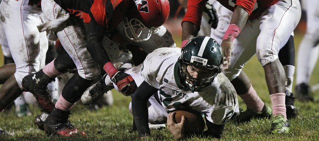 Free State's Carson Bowen (22) squirts though Wyandotte defenders for on Friday, Oct. 18, 2013.