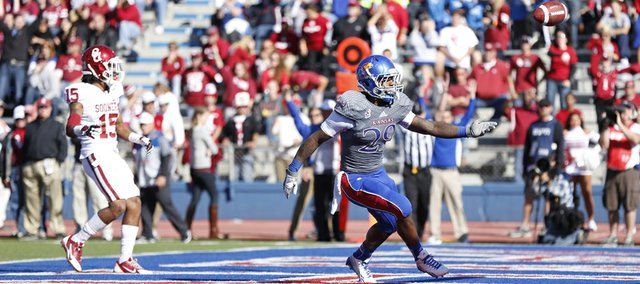 Kansas running back James Sims flips the ball to an official after scoring a touchdown against Oklahoma during the second quarter on Saturday, Oct. 19, 2013 at Memorial Stadium.