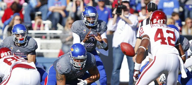 Kansas quarterback Montell Cozart takes a snap against Oklahoma during the second quarter on Saturday, Oct. 19, 2013 at Memorial Stadium.