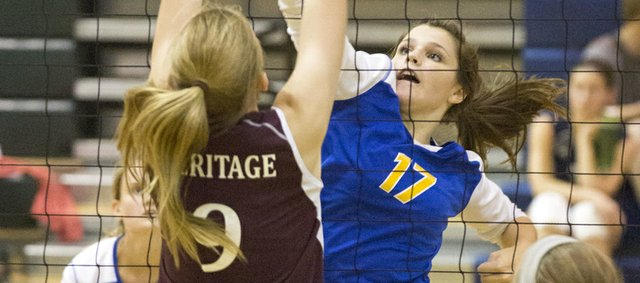 Veritas' Allison Swisher hits a ball at the net past a Heritage blocker during their game Tuesday evening at Bishop Seabury.