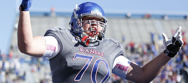 Kansas offensive lineman Gavin Howard raises up the crowd after tight end Jimmay Mundine's touchdown against Oklahoma during the first quarter on Saturday, Oct. 19, 2013 at Memorial Stadium.