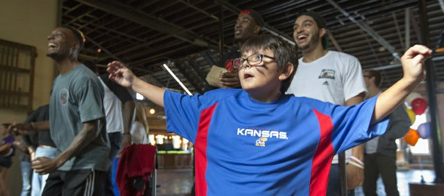 Hunter Lavallie, 11, of Lawrence shows off his dance moves as he competes, and eventually beats, Kansas basketball player Naadir Tharpe in a game of Dance Dance Revolution, Sunday afternoon at Abe & Jake's Landing. The event was part of an equipment drive put on by Bill and Cindy Self's Assists Foundation.